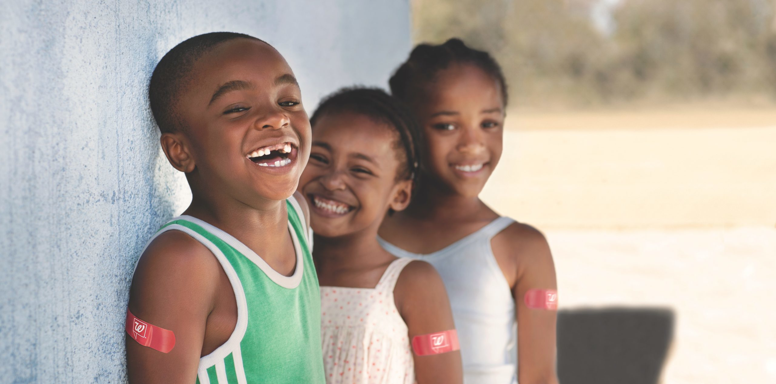 Boy and two children lean against blue wall with red Walgreens bandaid