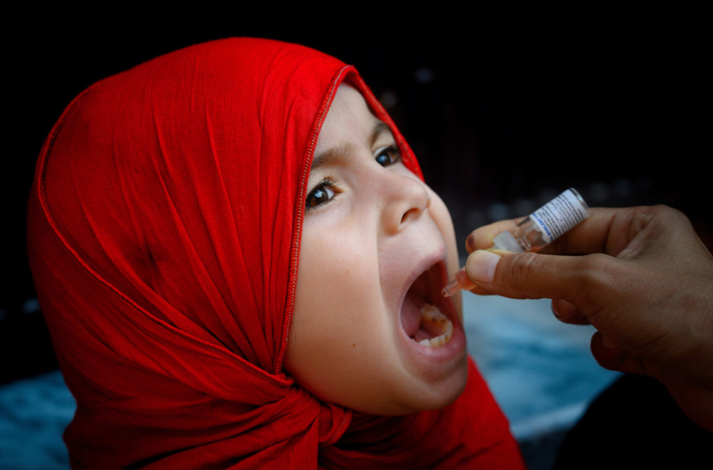 On 22 September 2020, a girl receives the polio vaccine in Rawalpindi, Pakistan. The country's first national polio vaccination campaign in September 2020 after a six-month pause due to COVID-19 reached over 39 million children under five years of age. More than 260,000 trained frontline workers went door to door and, in the context of COVID-19, were equipped with personal protective gear, to ensure the safety of children, caregivers and polio workers.