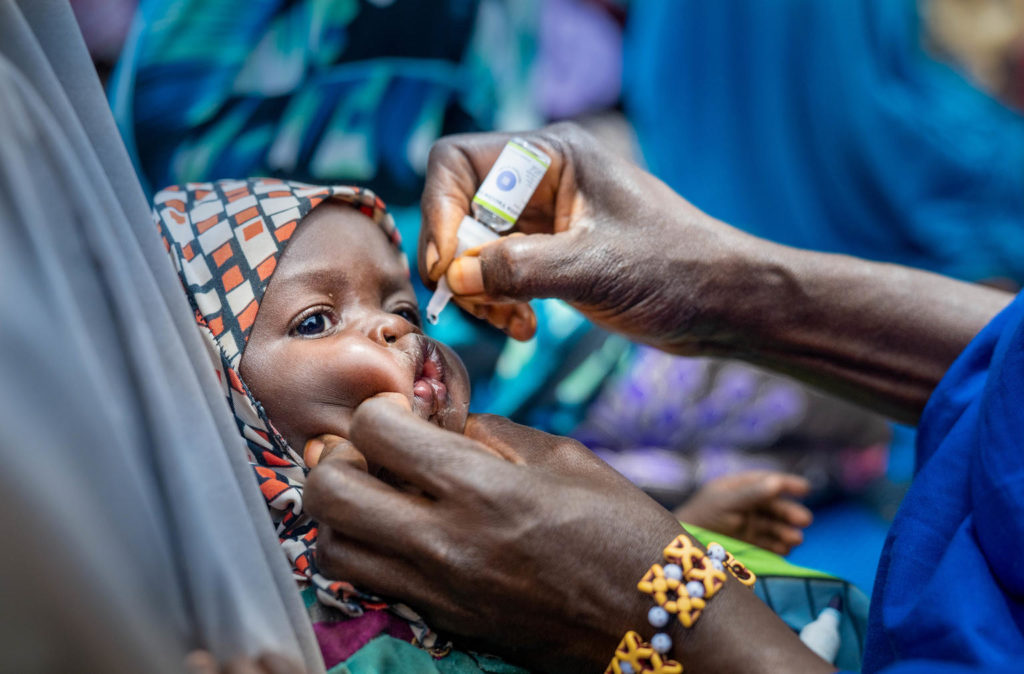 On 13 March 2020 in Fanisau Ugongo Village in Kano State, Nigeria, a Volunteer Community Mobilizer (VCM) receives a dose of the oral polio vaccine during a child naming ceremony. VCMs often take advantage of community gatherings such as naming ceremonies and other events to talk with parents and care-givers about vaccination and other healthy practices – and to vaccinate children against polio. Nigeria has crossed over three years without a single child being paralyzed by the wild polio virus and is on track to be certified wild polio virus free along with the African region in 2020. However, the government and GPEI partners continue supporting efforts to immunize the country's 55.5 million children under five years of age to maintain the 'zero polio case' status and rid the country of all forms of the polio virus.