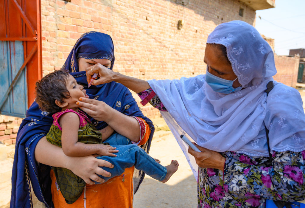 On 23 July 2020 in Faisalabad, Punjab, Pakistan, polio staff Razia Bano, age 48, marks the finger of an eight-month-old boy after he's received the polio vaccine, as he sits in his mother's lap.